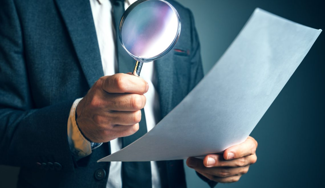 Lawyer reading legal contract agreement disclaimer with magnifying glass, person in elegant business suit reading document.