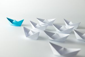 Leadership concept with blue paper ship leading among white